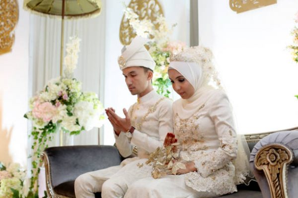 A pair of newlywed Muslim bride and groom seated for prayers at 'pelamin' (a decorated newlywed seating at the main stage) in wedding reception, Kuala Lumpur Malaysia.